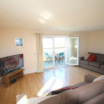 Spacious open plan lounge, kitchen diner with patio doors to balcony and views over fistral