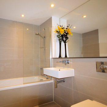 Ocean gate bathroom with shower over bath, chrome heated towel rail